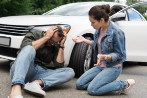 a woman trying to help a man she just hit with her car